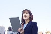 ビル群の前でタブレットで検索する働く女性