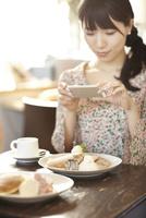 カフェにてパンケーキを携帯電話で撮影する女性