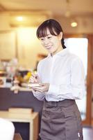 カフェにて接客をして働く女性