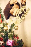クリスマスツリーに飾りつけをする男の子
