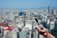 携帯電話と街並み 10133000295| 写真素材・ストックフォト・画像・イラスト素材|アマナイメージズ