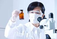 薬品の瓶を持つ研究者