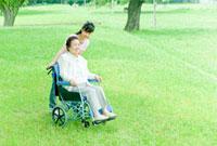 車椅子のシニア女性と押す看護師