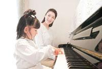 ピアノを弾く娘と見守る母親
