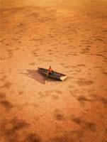 干上がった土地を古い手漕ぎボートで進む男性