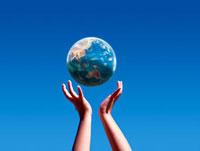 空にかざした手の上で浮かぶ地球