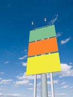 青空にそそり立つ三面のカラフルな看板
