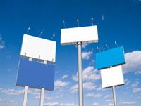 青空にそそり立つ青と白の五面の看板