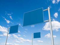 青空にそそり立つ三つの道路標識