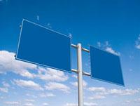 青空にそそり立つ二面の道路標識