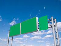 青空にそそり立つ三面の高速道路標識