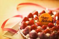 キャンドルを立てた苺のバースデーケーキとリボン