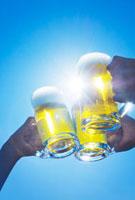 青空の中でジョッキビールで乾杯をする3人