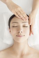 ベッドに仰向けで顔にマッサージを受ける女性