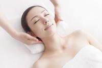 ベッドに仰向けで首にマッサージを受ける女性