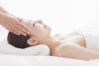 ベッドに仰向けで頭にマッサージを受ける女性