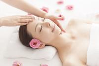 耳元に花を挿しベッドに仰向けで顔にマッサージを受ける女性