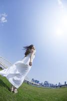 都会の青空の下で空を見上げる女性