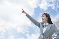 桜と青空をバックに空を指さす女子高生