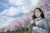 桜並木をバックに、卒業証書を持って微笑む女子高生