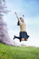 桜並木の前で思いっきりジャンプする女子高生