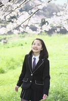 桜並木の下で笑う女子中学生