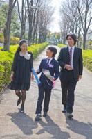 卒業証書と花を持って歩く少年と両親