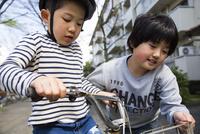 男の子に自転車を乗れるように練習させる女の子