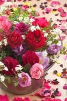 バケツに生けたバラの花と花びらとポプリ