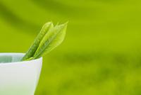 湯呑みに入った一番茶のお茶の葉と茶畑