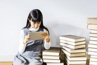 山積みの本の中でタブレットpcを見つめる少女