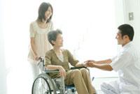 車椅子の患者の手を握る医師