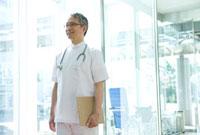 病院の玄関に立つ医師