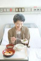 ベッドの上で食事を取る年配の患者