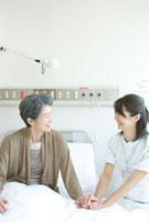 年配患者の手を握る笑顔の看護婦