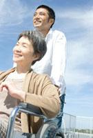 車椅子の母親を押す息子