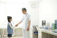 握手をして笑う少女と医師