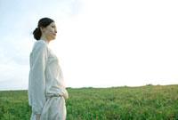 草原に立ち景色を眺める30代女性の横顔