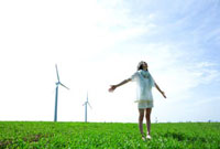 青空の草原で風車を背に胸を反らす30代女性