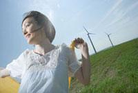 風車を背にストールをなびかせる笑顔の30代女性