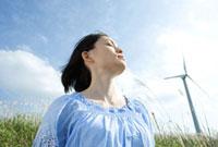 風車を背に草原に立つ30代女性