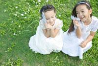 野原で羽を手に笑うの女の子二人
