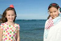 青空の海岸で微笑む女の子2人