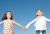 手をつなぎ空を見上げる女の子2人