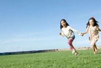 手をつなぎ野原を駆ける女の子2人