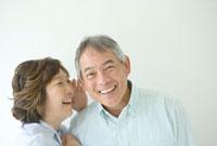 笑顔で耳打ちするシニア夫婦