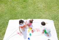 芝生の上でペンキで絵を描く子供三人