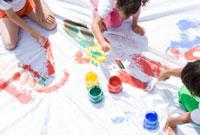 ペンキで絵を描く子供三人