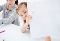 スケッチブックに描いた絵を見せる女の子