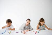 テーブルに並びクレヨンで絵を描く子供三人